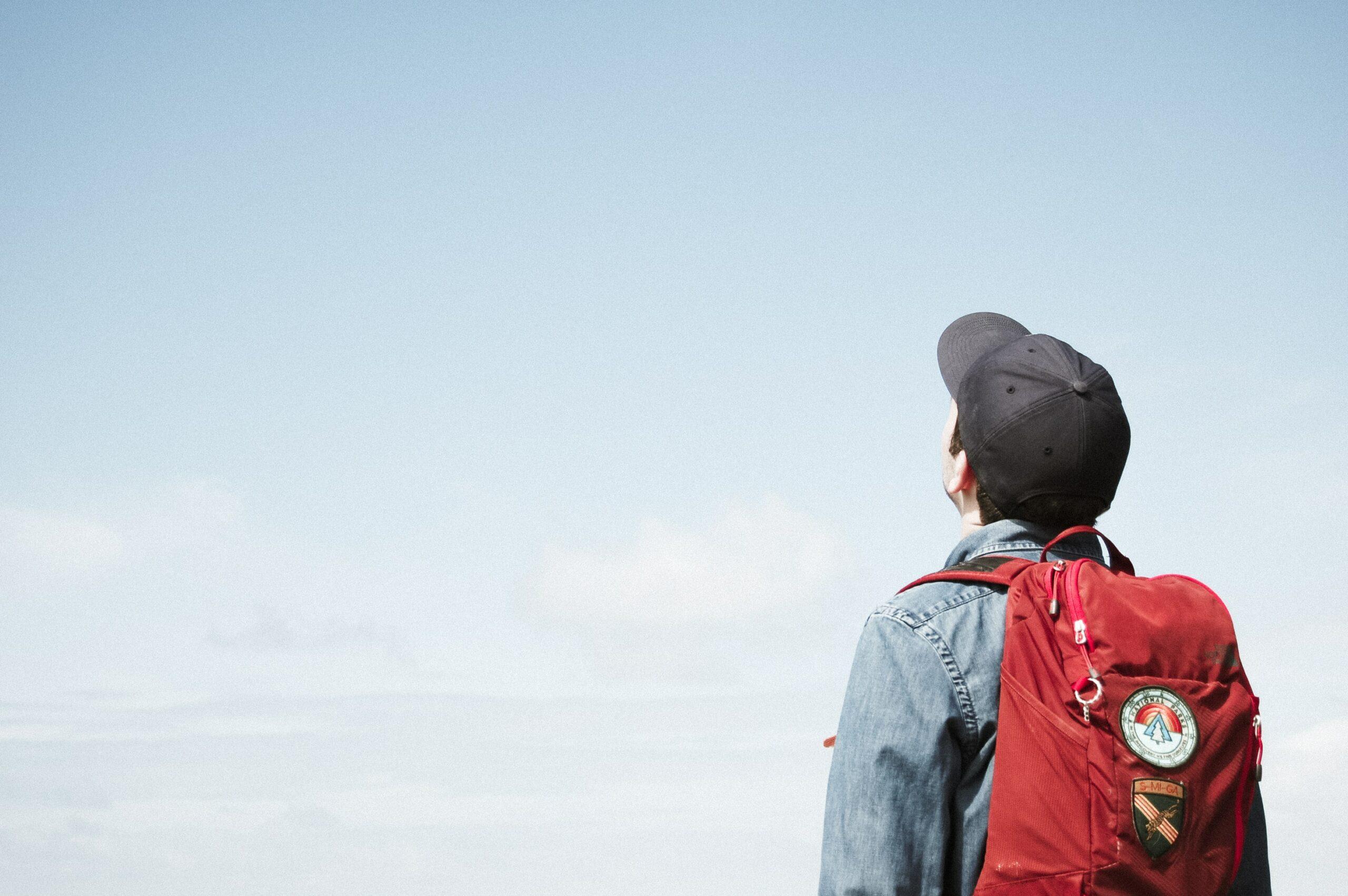 Poika katsoo siniselle taivaalle punainen reppu selässään.