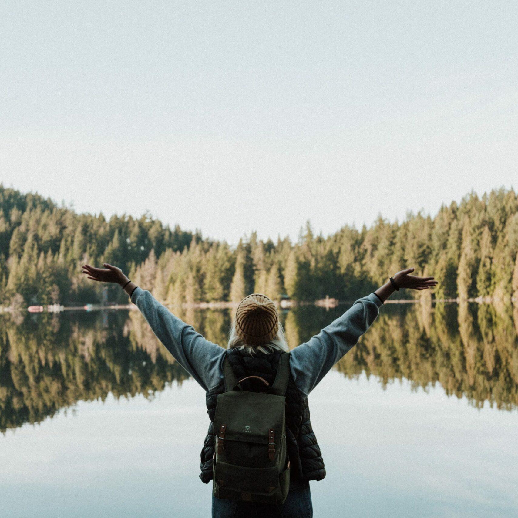 Nainen seisoo veden äärellä kädet nostettuna ilmaan.