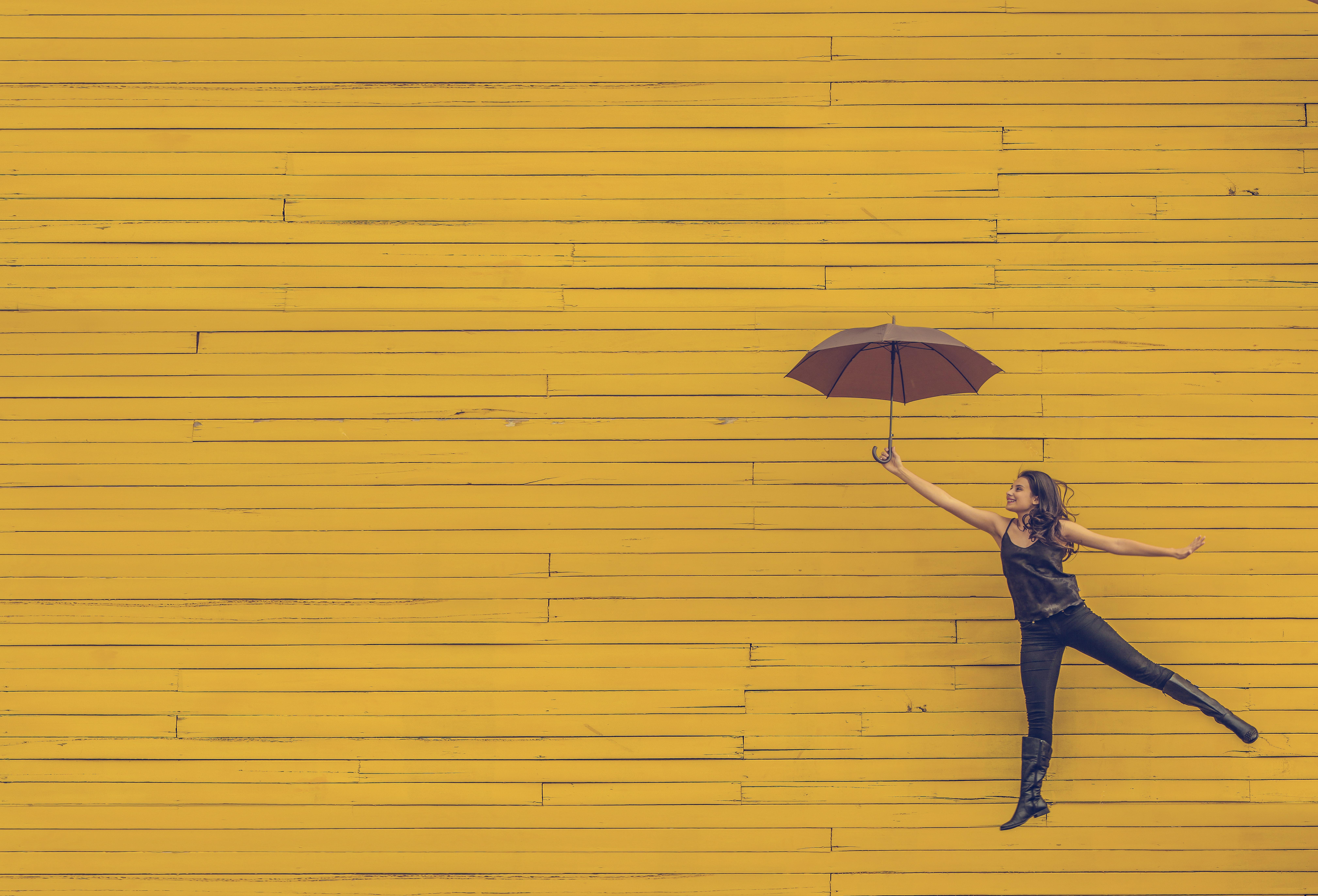 Tyttö hyppää sateen varjo kädessä. Taustalla keltainen lautaseinä.
