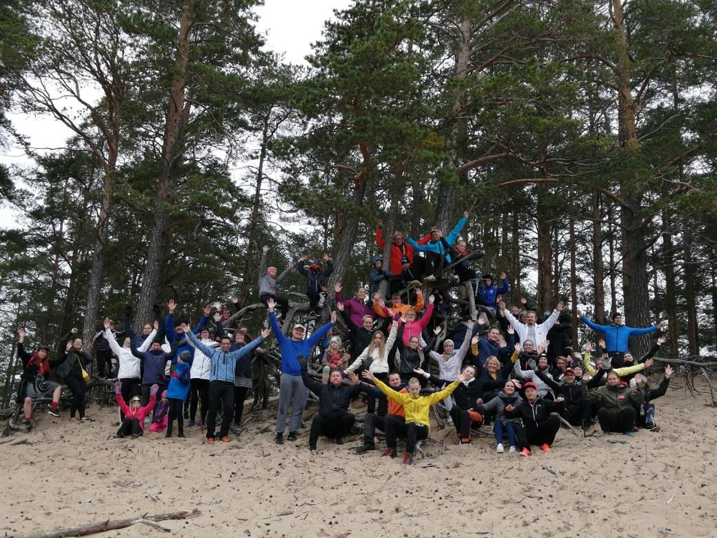 Kuvituskuva. ihmisiä ryhmäkuvassa hiekalla, takana mäntyjä