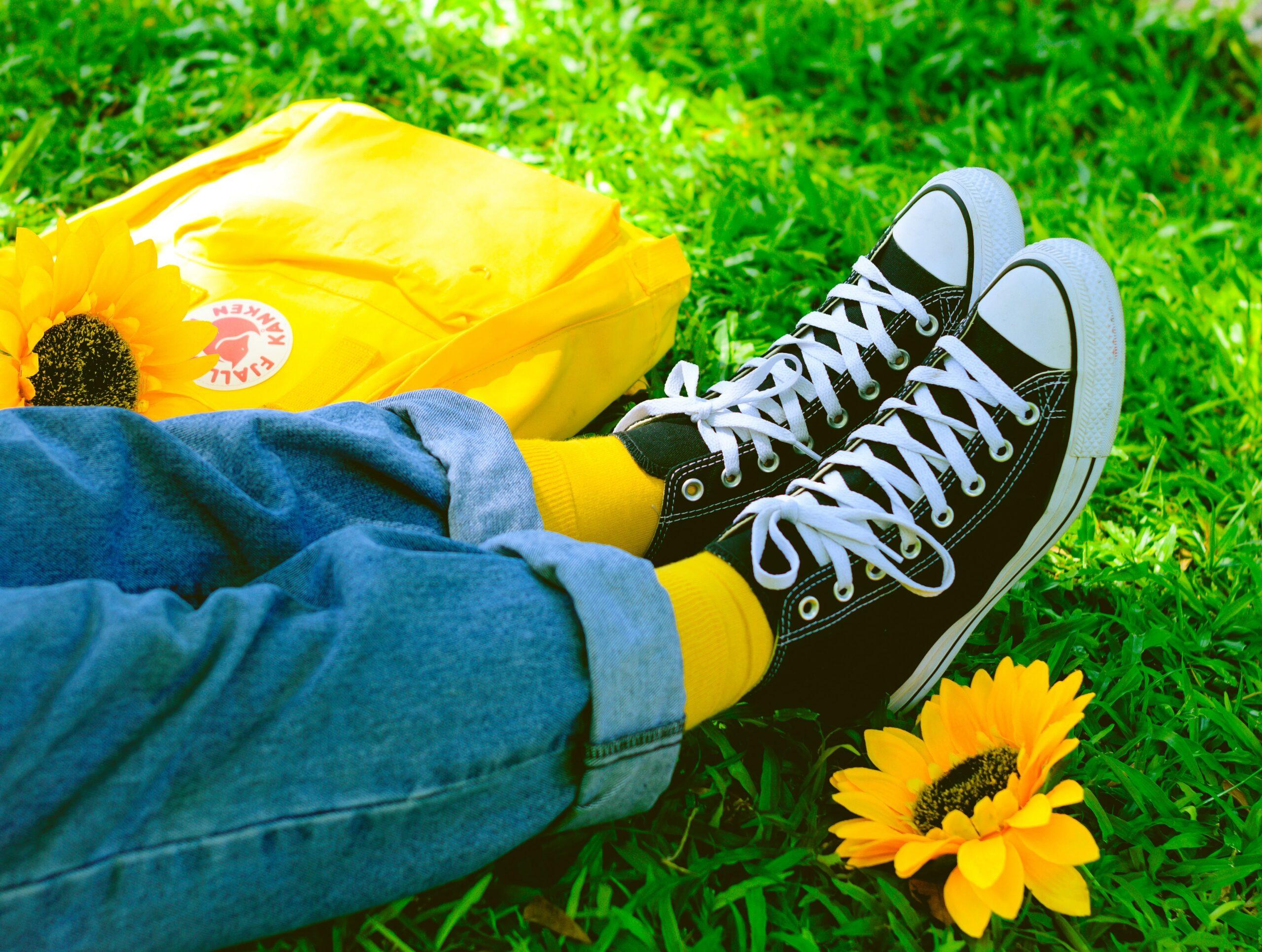 Jalat joissa mustat tennarit ja vierellä keltainen reppu sekä auringonkukkia.