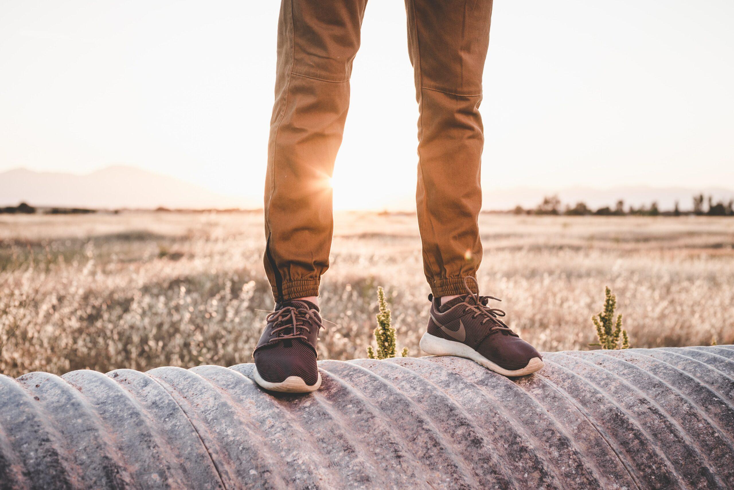 Ihminen seisoo matellisen putken päällä. Taustalla vilja pelto.